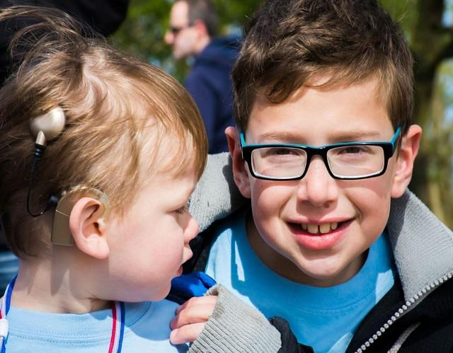 2 boys young boys - 1 with cochlear implant