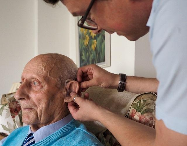 JDA staff helping man with hearing aid