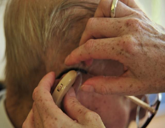Elderly man having help putting hearing aid in