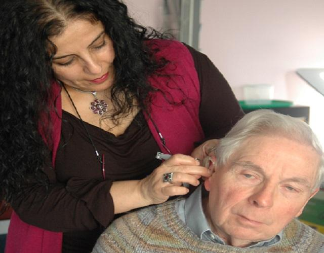 Lady helping man with hearing aid