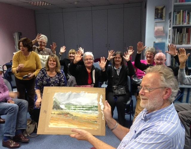 Artist holding up painting with happy members sitting behind